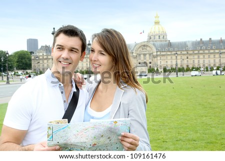 Couple reading tourist map in front of the Invalides building - stock photo