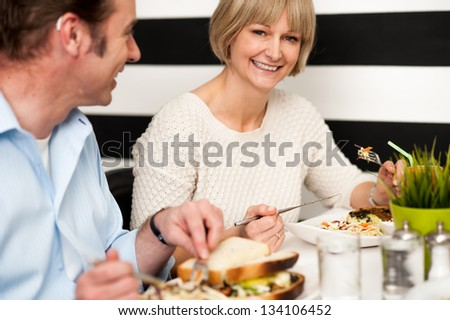 Couple recalling old memories while dining in a food court. - stock photo