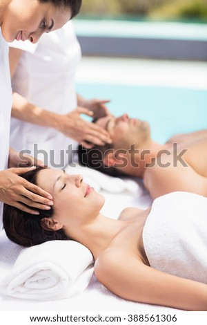 Couple receiving a head massage from masseur in a spa - stock photo