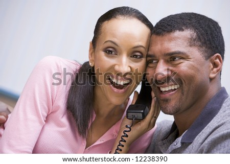 Couple receiving good news over phone at home - stock photo