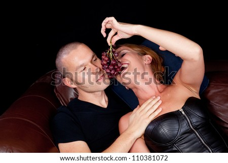 Couple reclining on a couch together, she is feeding him grapes by dangling them for him to bite