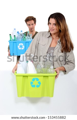 Couple recycling boxes of plastic bottles - stock photo