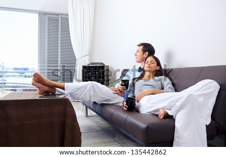 Couple relax at home with cup of coffee and sofa couch. happy healthy relationship - stock photo