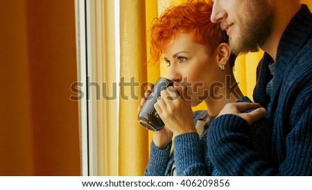 Couple relax together in home looking through the window. Romantic happy cozy good morning. Love and family couple. Man embracing hugging his girlfriend. Woman looks out the window. Husband and wife. - stock photo