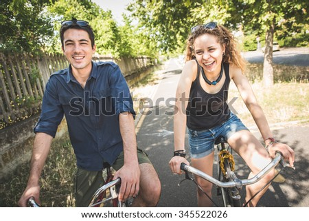 Couple relaxing after a ride in the park with bicycles. Healthy lifestyle, couples and people concepts - stock photo