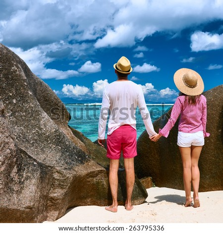 Couple relaxing among granite rocks on a tropical beach Anse Source d'Argent at Seychelles, La Digue.  - stock photo
