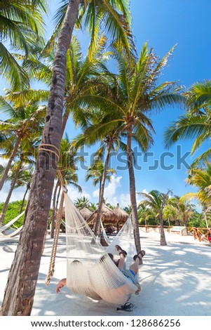 Couple relaxing in a hammock, Mexico - stock photo