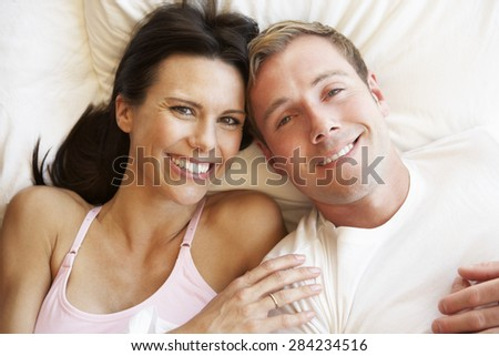 Couple Relaxing In Bed - stock photo