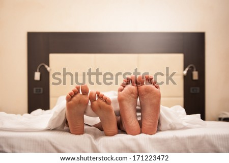 Couple relaxing in hotel room under sheets. Close up on feet. - stock photo