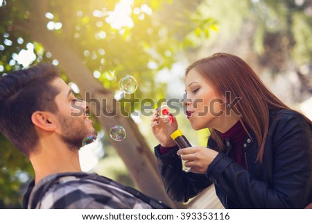 Couple relaxing in the park with bubble blower, selective focus - stock photo