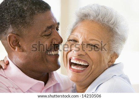 Couple relaxing indoors laughing - stock photo