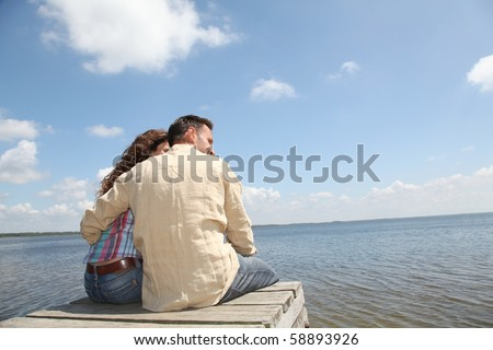Couple relaxing on a pontoon - stock photo