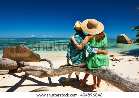 Couple relaxing on a tropical beach Anse Source d'Argent at Seychelles, La Digue.  - stock photo