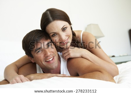 Couple Relaxing On Bed At Home - stock photo