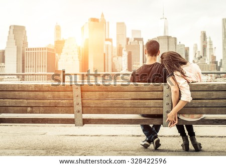 couple relaxing on New york bench in front of the skyline at sunset time. concept about love,relationship, and travel  - stock photo