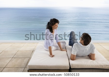 Couple relaxing on sun beds on terrace overlooking sea, elevated view