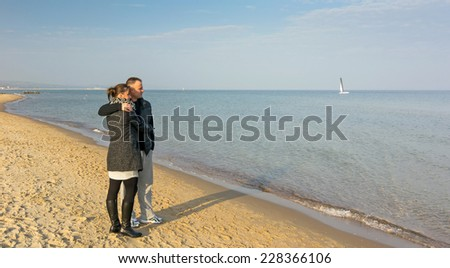 Couple relaxing on the autumn sea beach