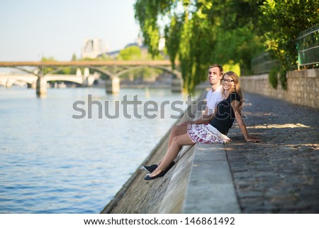 Couple relaxing on the bank of the Seine - stock photo