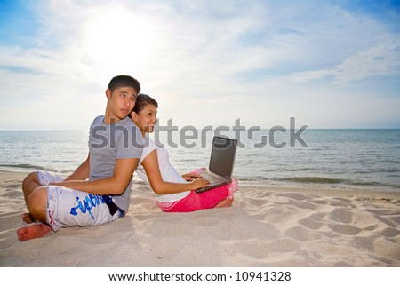 couple relaxing on the beach while one of them happily working on laptop