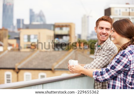 Couple Relaxing Outdoors On Rooftop Garden Drinking Coffee - stock photo