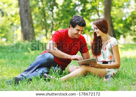 Couple relaxing together in summer park with tablet computer pc having fun