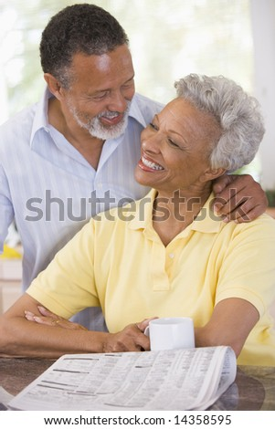 Couple relaxing with a newspaper smiling - stock photo