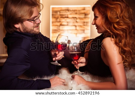 Couple relaxing with glass of red wine at romantic fireplace on winter evening time. Smiling and looking at each other. Image toned. Horizontal