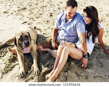 couple relaxing with pet dog on the beach. - stock photo