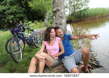 Couple resting by a lake - stock photo