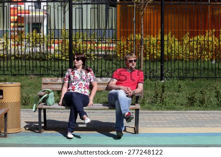 Couple resting on a bench in the park - stock photo