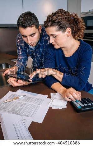 Couple reviewing their accounts with a digital tablet - stock photo