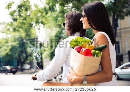 Couple riding a scooter in town while woman holding a shopping bag full of groceries - stock photo