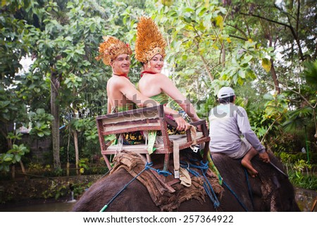 couple riding and traveling on an elephant at asia - stock photo