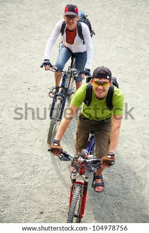 Couple riding bicycle on the road - stock photo