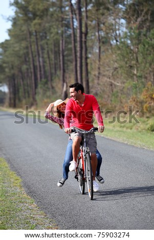 Couple riding bicycles in countryside - stock photo