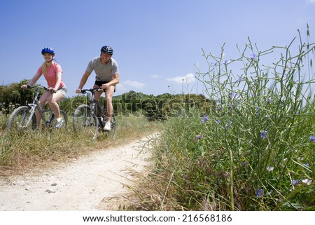 Couple riding bicycles on rural path