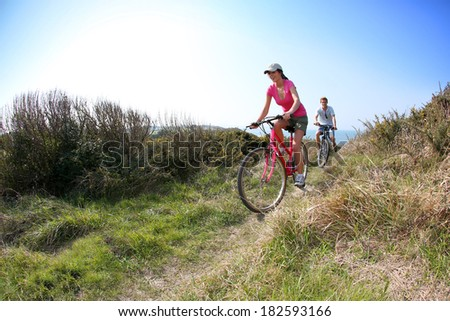 Couple riding bike on country path - stock photo