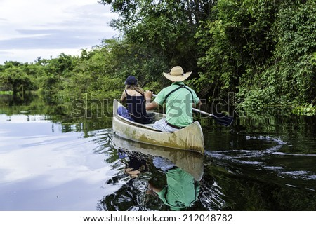 Couple riding canoe in Pantanal River, Brazil - stock photo