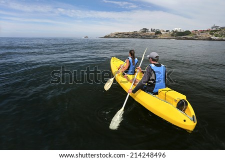 Couple rowing in a kayak on a calm ocean and enjoying a beautiful day. - stock photo