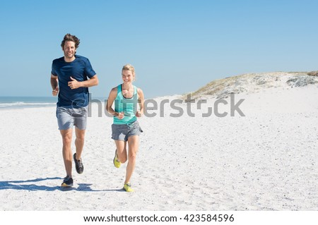 Couple runners exercising on a sandy beach with copy space. Couple running on beach training for marathon run. Athletic attractive man and young woman jogging in a summer day. - stock photo