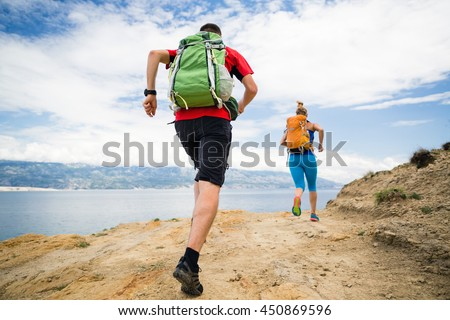 Couple runners running with backpacks on rocky trail at seaside and mountains. Young woman and man trail running on mountain path looking at beautiful inspirational landscape view. - stock photo