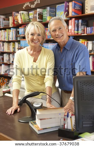 Couple running bookshop - stock photo