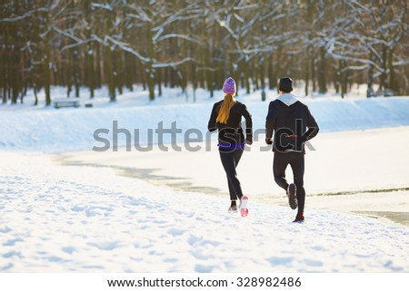 Couple running during winter - stock photo