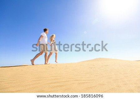 Couple running having fun holding hands under sun in playful and romantic relationship under sun and blue sky in desert. Two young lovers cheerful together on romance in summer. Joyful man and woman. - stock photo
