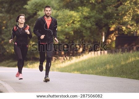 Couple running in the park - stock photo