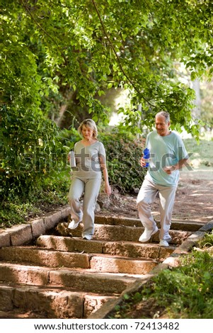 Couple running in the wood - stock photo