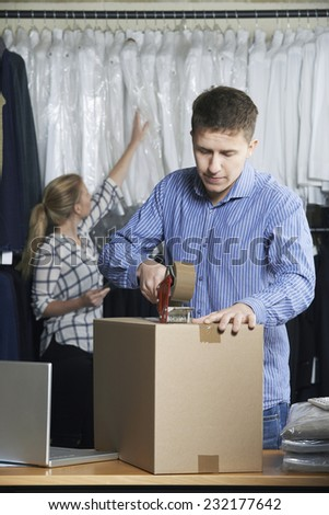 Couple Running On Line Clothing Store Packing Goods For Dispatch - stock photo
