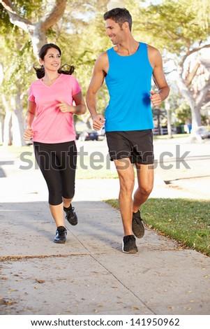 Couple Running On Suburban Street - stock photo