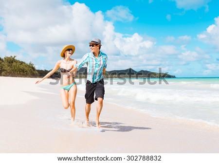 Couple running on the beach.  - stock photo