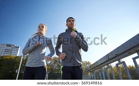 couple running outdoors - stock photo